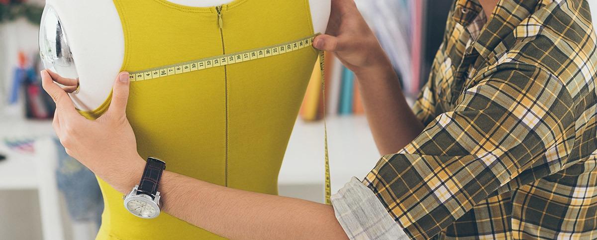 Ammattilainen mittaa vaatetta mannekiinin päällä